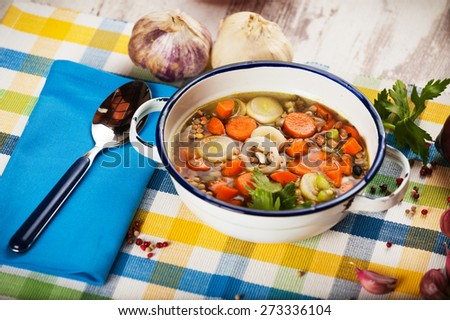 Vegetable soup in a metal bowl on a rural rustic wooden table. - stock photo