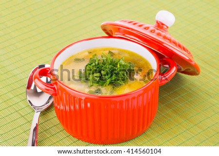 Vegetable soup in bowl on green bamboo background. - stock photo