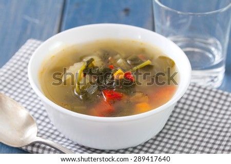 vegetable soup in white bowl with spoon and glass of water