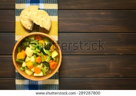 Vegetable soup made of zucchini, green bean, carrot, broccoli, potato and pumpkin in wooden bowl with a bun on kitchen towel, photographed overhead on dark wood with natural light - stock photo