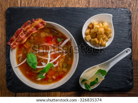 Vegetable soup served with bacon, cheese and croquettes - stock photo
