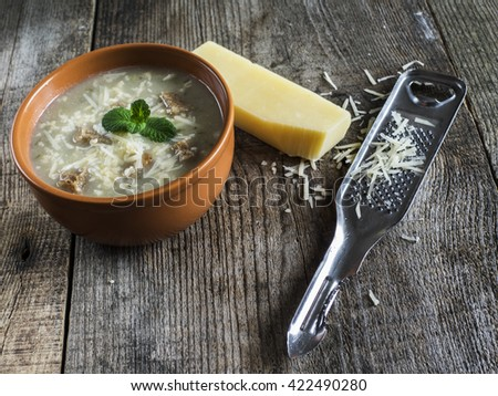 vegetable soup with croutons and grated cheese on old weathered wooden surface - stock photo