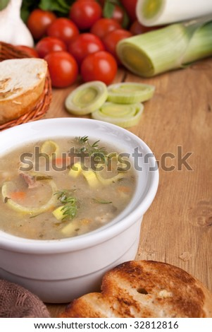 vegetable soup with ingredients on wooden table