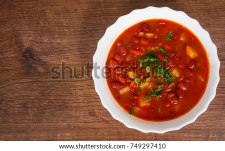 Vegetable soup with red bean, tomato on a wooden background. with copy space. top view