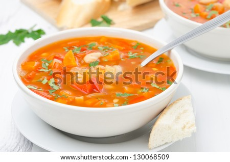 Vegetable soup with white beans in a bowl and spoon on a white table horizontal