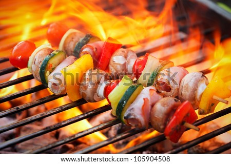 vegetable spit on grill flames in background - stock photo
