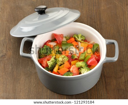 Vegetable stew in gray pot on wooden background