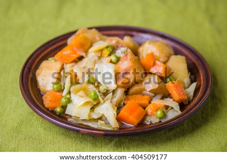 Vegetable stew. Vegetarian food. Close-up of a brown plate on a green background.
