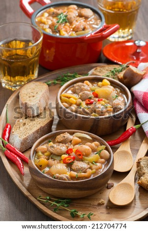 vegetable stew with sausages in a wooden bowl, vertical, top view, close-up