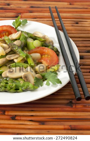 Vegetable stir-fry with chopsticks against a bamboo background