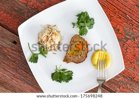 Vegetable stuffed meatloaf served with rice pilaf and mashed potato, garnished with parsley on picnic table - stock photo