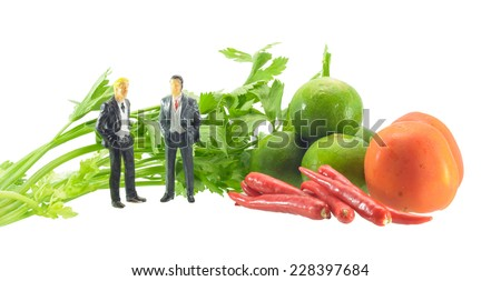 vegetable tomatoes, lemon ,parsley and pepper with businessman miniature isolated on white
