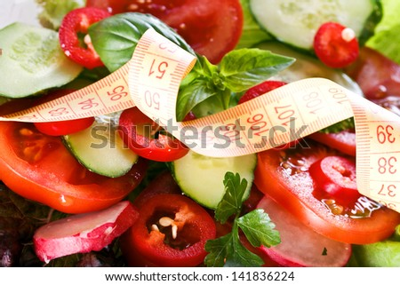 Vegetables and centimeter. Centimeter on the background of salad - stock photo