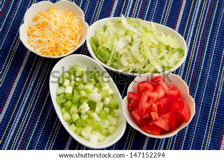 Vegetables and Cheese Four white bowls filled with scallions, lettuce, tomato, and cheese.  The bowls are placed on a woven blue, multi colored cloth.