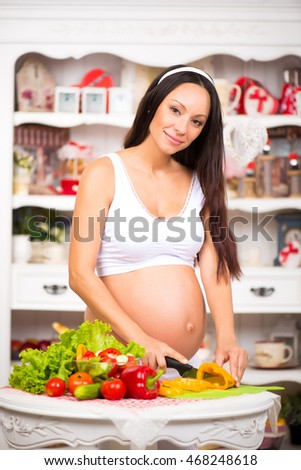 Vegetables and diet during pregnancy. Beautiful pregnant woman in the kitchen preparing a meal