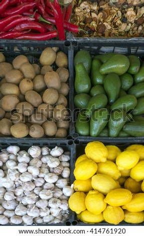 vegetables and fruit on the counter: garlic, chilli, ginger, avocado, lemons, kiwi, dried fruit