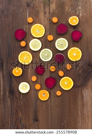 Vegetables and fruit slices on old wooden background - stock photo