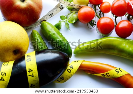 vegetables and fruits for weight loss, a measuring tape, diet, weight loss,cherry tomatoes, green peppers.cucumber.eggplant