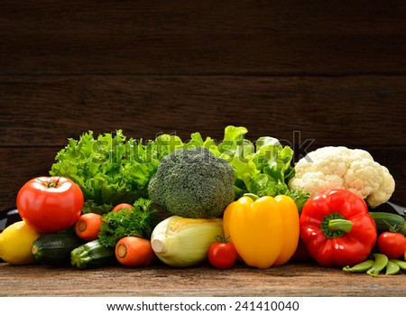 Vegetables and fruits on old wooden background - stock photo