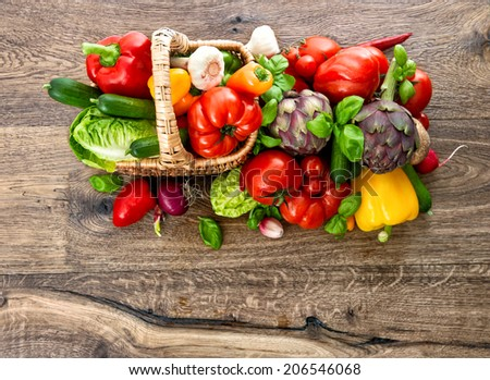 vegetables and herbs in basket on wooden background. fresh raw food. top view. selective focus - stock photo