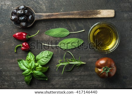 Vegetables and herbs on dark rustic wooden background. Greek black olives, fresh green sage, rosemary, basil herbs, oil, tomato, peppers.  Top view - stock photo