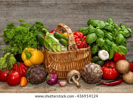 Vegetables and herbs on rustic wooden background. Raw food ingredients - stock photo