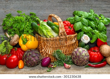 Vegetables and herbs on wooden background. Fresh food ingredients. Country style picture. selective focus - stock photo