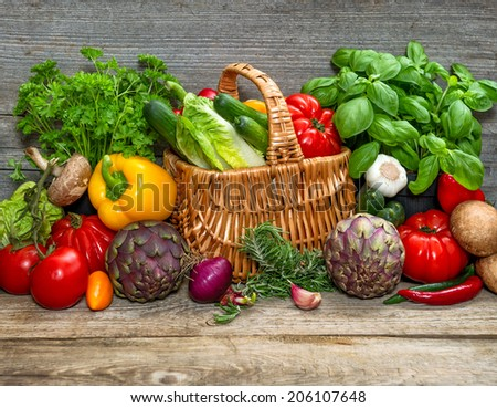 vegetables and herbs on wooden background. fresh raw food ingredients. country style picture. selective focus - stock photo