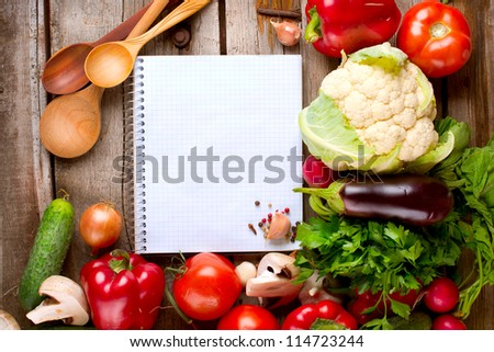 Vegetables and Spices on a Wooden Background and Paper for Notes.Open Notebook and Fresh Vegetables Background.Diet.Dieting.Space For Your Text - stock photo