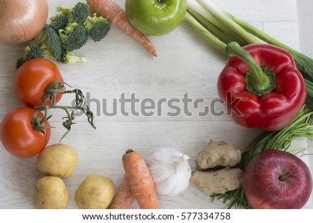 Vegetables arranged in a frame around a wooden board with space for copy