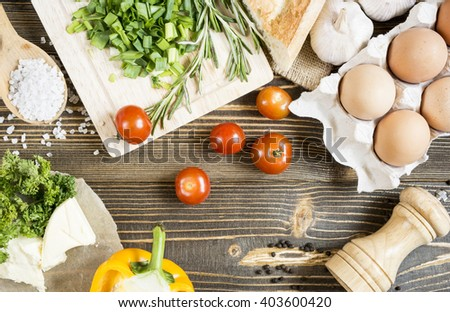 Vegetables green eggs oil salt dishes on the gross agricultural old wooden table top view - stock photo