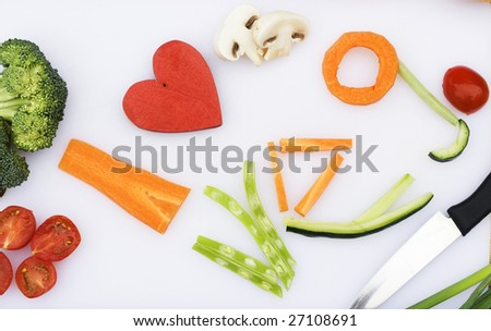 Vegetables have been used to spell Veg.  Carrots, beans, cucumbers, tomatoes, mushrooms and broccoli are the vegetables.  A red wooden heart has been used for 'love'. - stock photo
