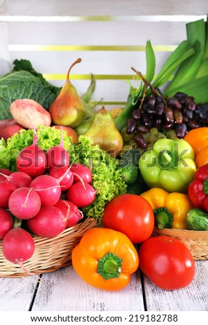 Vegetables in basket on white wooden box background - stock photo