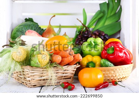 Vegetables in baskets on white wooden box background - stock photo