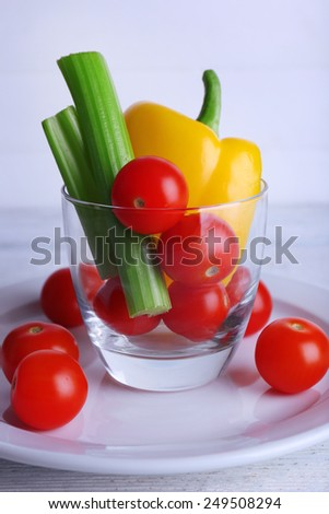 Vegetables in glass on plate and on color wooden planks background