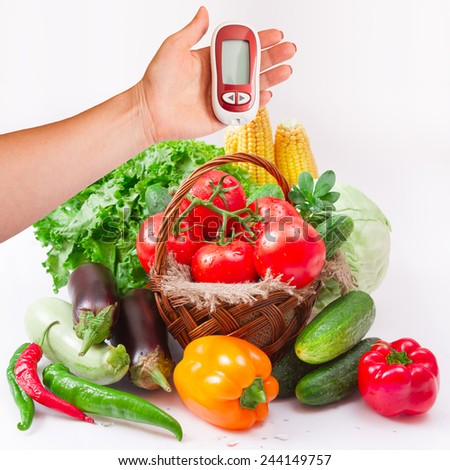 Vegetables isolated on white ( macro). Woman testing for high blood sugar. Woman holding device for measuring blood sugar.