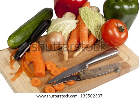 Vegetables, knife and peeler on cutting board isolated on white background