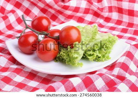 Vegetables on a square plate. Red tomatoes on a branch, lettuce. Organic vegetables. The cherry tomatoes on a branch. Ingredients for cooking.  Tomatoes and leafy green lettuce. - stock photo