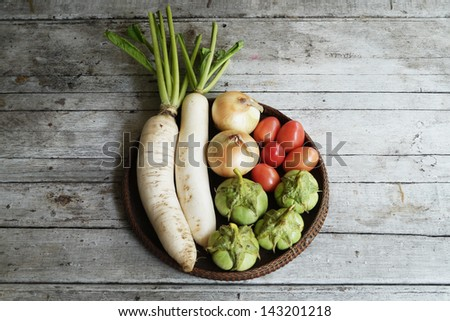 vegetables on  a wooden ,Radish, eggplant ,tomato and onions - stock photo