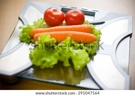 Vegetables on bathroom scales - stock photo