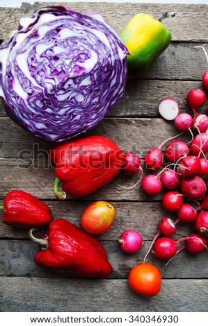 Vegetables on vintage wood background - autumn harvest. Fresh vegetable on wooden table. Top view. Autumn harvest: blue cabbage, radishes, tomatoes, peppers . Autumn background. Ripe vegetables. - stock photo