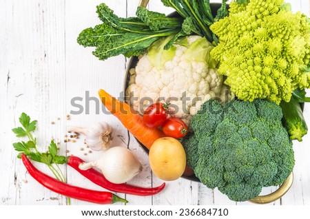 Vegetables on white rustic background.Winter veggies, broccoli, cauliflower,romanesco broccoli, carrots, potatoes,onion, tomatoes, kale, chile peppers - stock photo