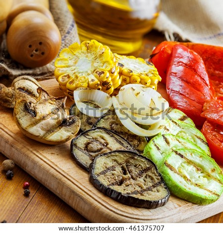 Vegetables roasted on a grill: tomato, corn, eggplant, mushroom, bell pepper, marrow and onion. Delicious healthy food for lunch. Close-up shot.