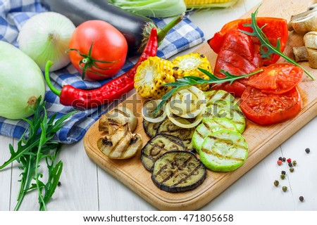 Vegetables roasted on a grill: tomato, corn, eggplant, mushroom, bell pepper, marrow and onion. Delicious healthy food and ingredients on a table. Close-up shot.