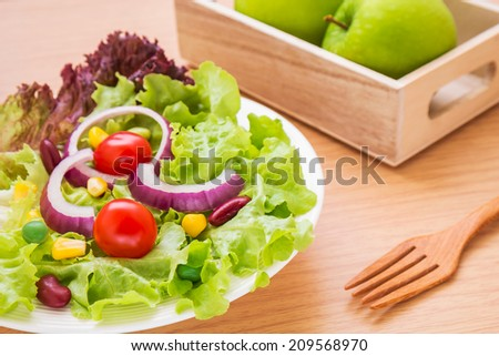 Vegetables salad on plate and green apple  - stock photo