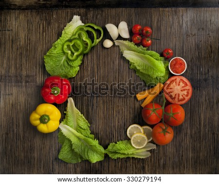vegetables shaping a circle on wooden background - stock photo