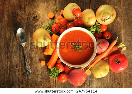 Vegetables soup surrounded by fresh vegetables and a spoon on a wooden background - stock photo