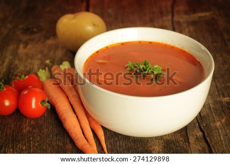 Vegetables soup surrounded by fresh vegetables on a rustic background - stock photo