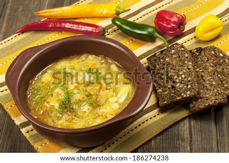 Vegetables soup with cabbage in bowl on  wooden background  - stock photo
