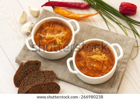Vegetables soup with cabbage in bowl on wooden table - stock photo